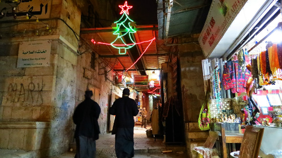 """This photo of a couple of priests walking through the Christian Quarter in Jerusalem was taken by James Cheatham, who has lived and worked on and off in the city since 2002.<br /> <br />""""When I was walking through the Christian Quarter, several of the shops had Christmas music playing such as Bing Crosby (White Christmas), Nat King Cole (Chestnuts Roasting On An Open Fire), and O Holy Night, amongst others which really added to the atmosphere,"""" said the native Californian."""
