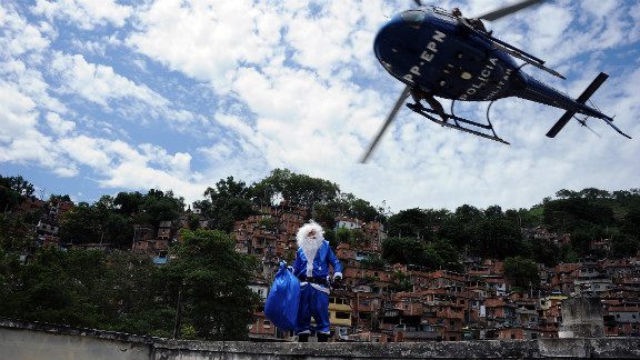 A militarized police helicopter leaves a Santa Claus atop a school in a shantytown, or favela, of Rio de Janeiro on Thursday, December 20. This St. Nick, dressed in the white and blue colors of Peace Police Units, handed out toys among the children in the Brazilian slum.