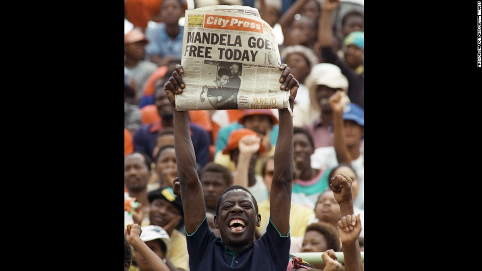 A jubilant South African holds up a newspaper announcing Mandela's release from prison at an ANC rally in Soweto on February 11, 1990. Two days later, more than 100,000 people attended a rally celebrating his release from jail.