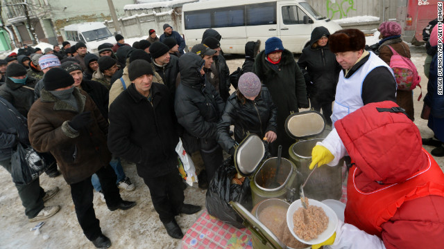 Homeless people queue to get free hot food in Kiev this week as a cold snap claims many lives.