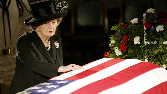"""Thatcher touches the flag-draped coffin of Reagan as he lies in state in the U.S. Capitol Rotunda in June 2004.  In a prerecorded video at his funeral, she called Reagan """"a great president, a great American and a great man."""" """"And I have lost a dear friend,"""" she said."""