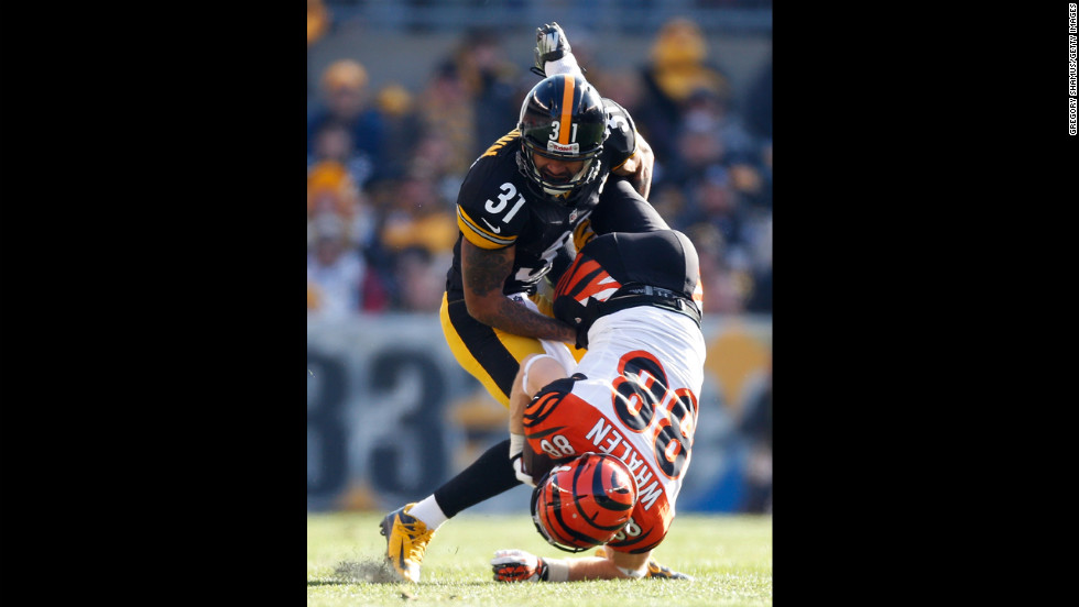 Ryan Whalen of the Bengals is tackled by Curtis Brown of the Steelers after a first quarter catch on Sunday.