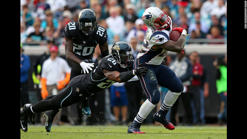 Stevan Ridley of the Patriots is tackled by Dawan Landry of the Jaguars on Sunday.