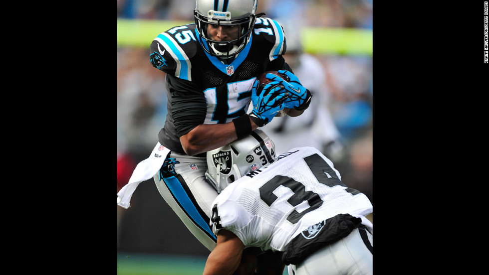 Joe Adams of the Panthers makes a catch as Mike Mitchell of the Raiders defends on Sunday.