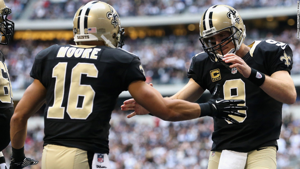 Drew Brees of the Saints celebrates a touchdown with Lance Moore against the Cowboys on Sunday.
