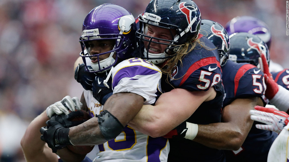 Adrian Peterson of the Vikings is stopped by No. 53 Bradie James and No. 58 Brooks Reed of the Texans on Sunday.
