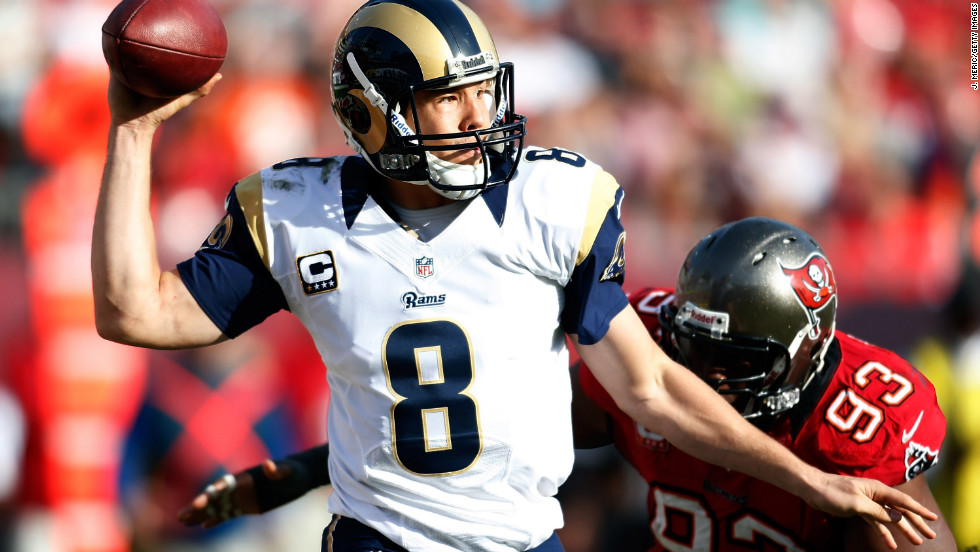 Quarterback Sam Bradford of the Rams throws a pass as defender Gerald McCoy of the Buccaneers closes in on Sunday.