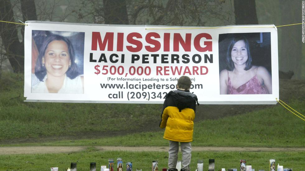 A young child stops to look at a makeshift memorial and a missing person's banner offering a half-million dollar reward for the safe return of Laci Peterson at the East La Loma Park  in Modesto, California, on January 4, 2003.