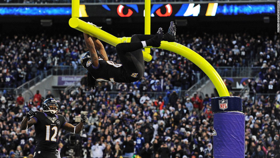 Wide receiver Torrey Smith of the Ravens hangs on the goal post after catching a touchdown pass during the first quarter on Sunday.