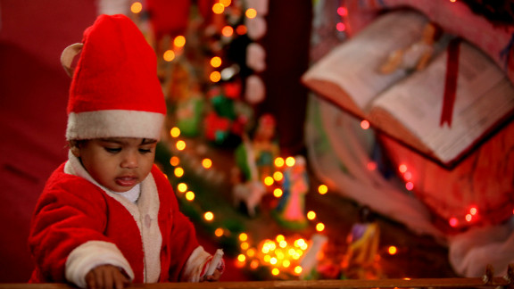 A young Indian child dressed as Santa Claus plays at a church, during Christmas celebrations in Jammu on December 25, 2012. Despite Christians forming a little over two percent of the billion plus population in India, with Hindus comprising the majority, Christmas is celebrated with much fanfare and zeal throughout the country.   AFP PHOTO/STR        (Photo credit should read STRDEL/AFP/Getty Images)