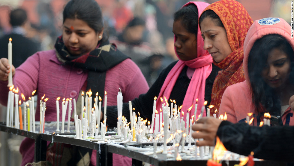 People light candles as they gather to pray during Christmas celebrations at The Sacred Heart Cathedral in New Delhi on Tuesday.