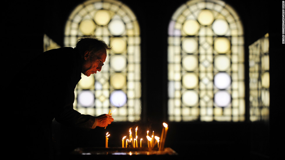 A sexton collects candles during a Christmas Mass in the golden-domed Alexander Nevsky Cathedral in Sofia, Bulgaria.