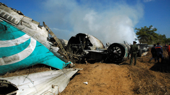 The crashed plane continues to smoke as rescue personnel survey the area.