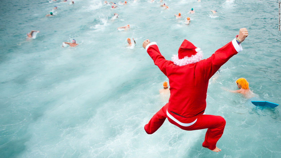 A competitor dressed  as Santa jumps into the water during the 103rd Barcelona Traditional Christmas Swimming Cup at the Old Harbour of Barcelona in Barcelona, Spain, on Tuesday, December 25.