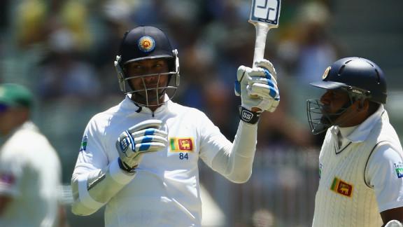 Kumar Sangakkara raises his bat after reaching 10,000 Tests in a record equaling feat.