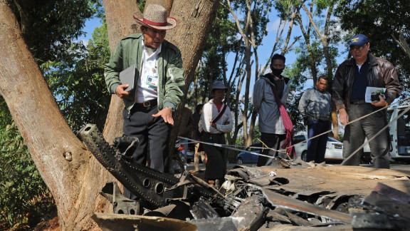 An officer from Myanmar's Department of Civil Aviation inspects the remains of the plane on December 26. An Air Bagan representative said the airline was investigating the crash.