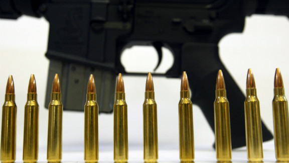 Several .223 caliber rounds near a Bushmaster XM-15; the manufacturer's owner is putting its gun companies up for sale.