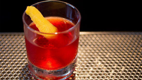 Place the peel right-side up in the glass for a nice visual of the bright yellow peel against the classic red cocktail.
