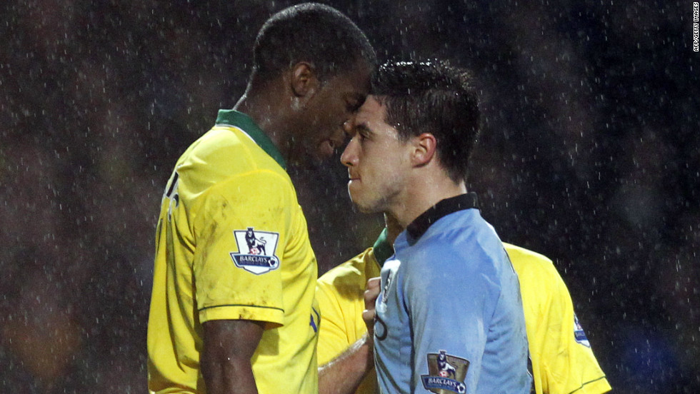 It was pouring down in Norwich, where second-placed Manchester City won 4-3 despite having Samir Nasri (R) sent off following this clash with Sebastien Bassong, who was booked.