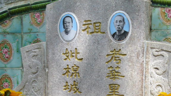 The tomb of Mr. and Mrs. Tan Yong Thian is seen in Bukit Brown cemetery with incense and recent offerings.