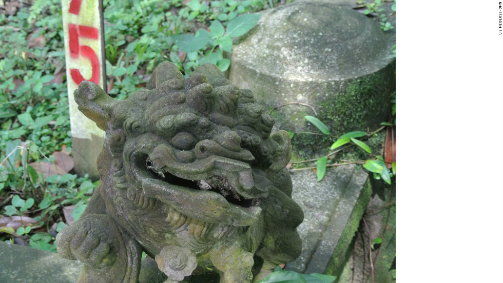 A guardian lion is seen on a grave marked for exhumation in Bukit Brown cemetery.