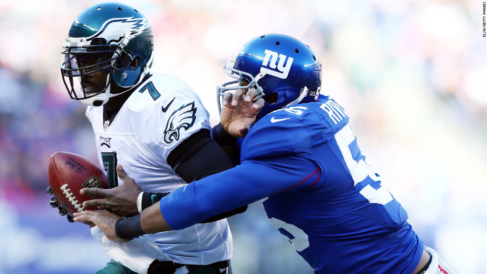 Michael Vick of the Philadelphia Eagles is pushed out of bounds by Keith Rivers of the New York Giants on Sunday.