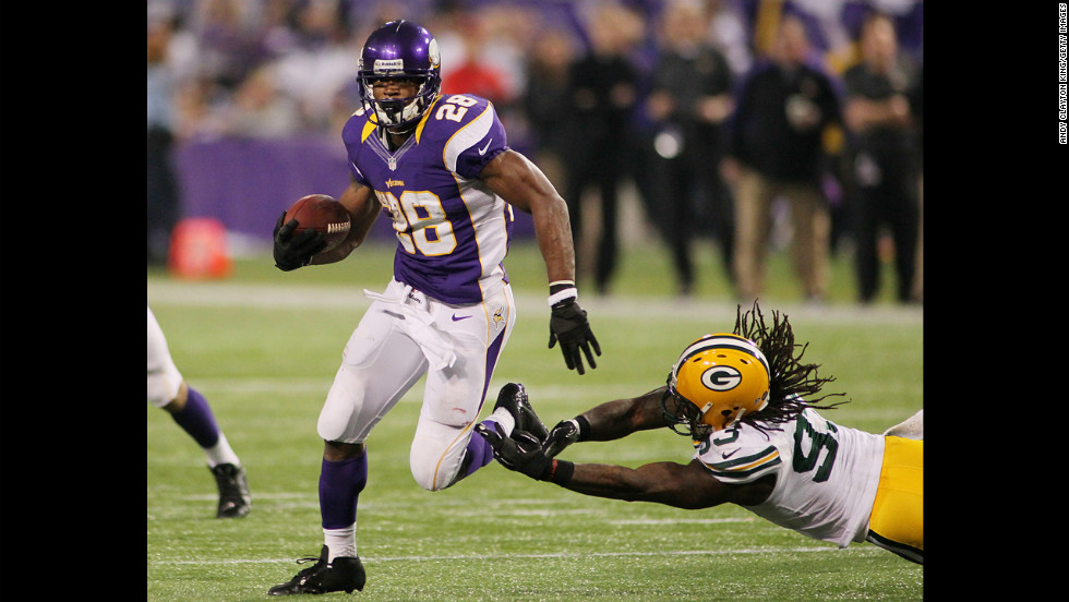 Adrian Peterson of the Minnesota Vikings runs past Erik Walden of the Green Bay Packers on Sunday.