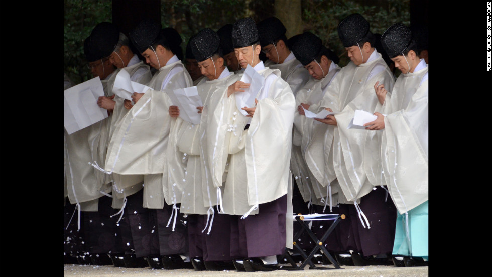 Shinto priests purify themselves with pieces of paper during a ritual end-of-the-year ceremony at Meiji Shrine in Tokyo on Monday. Millions of Japanese people visited shrines and temples across the country to celebrate the new year.