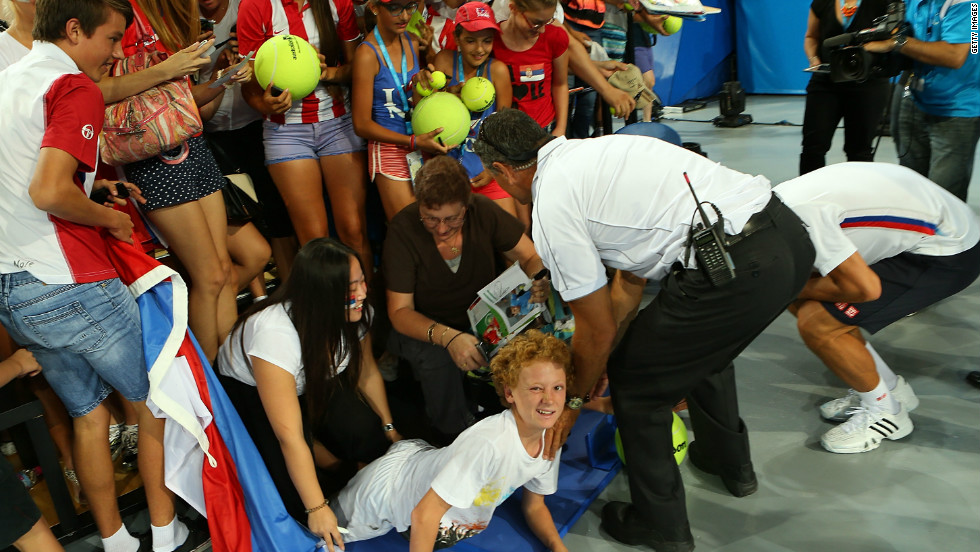Novak Djokovic goes down on his haunches after an spectator barrier collapsed as he was signing autographs.