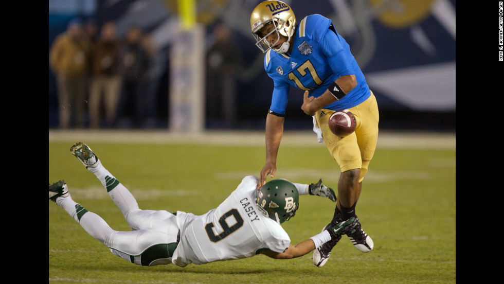 Quarterback Brett Hundley of the Bruins fumbles as Chance Casey of the Bears tackles him on December 27.