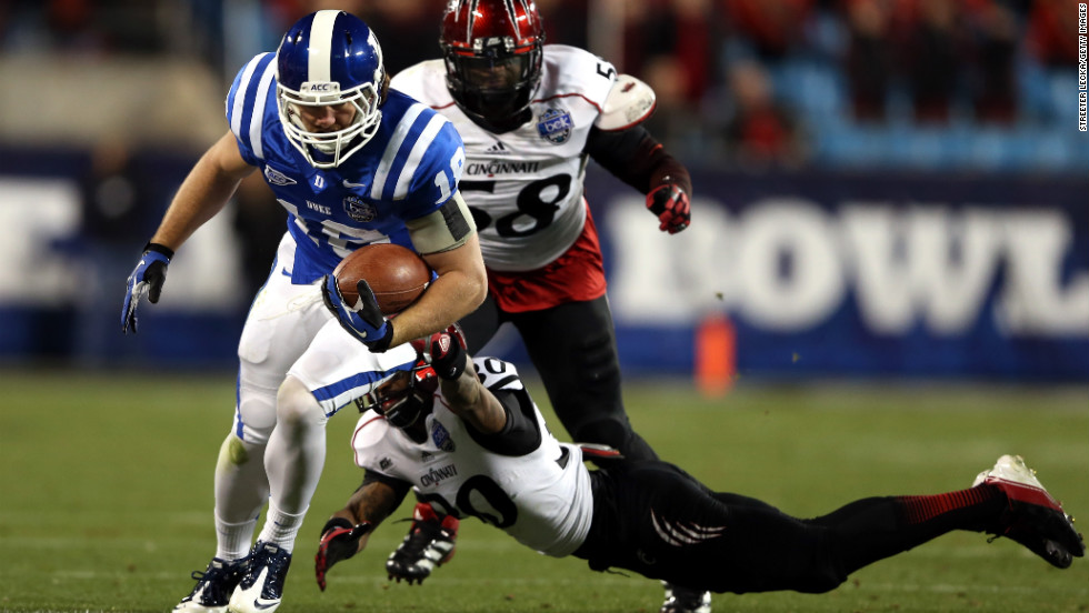 Aaron Roberson of the Cincinnati Bearcats dives for Brandon Connette of the Duke Blue Devils on December 27.