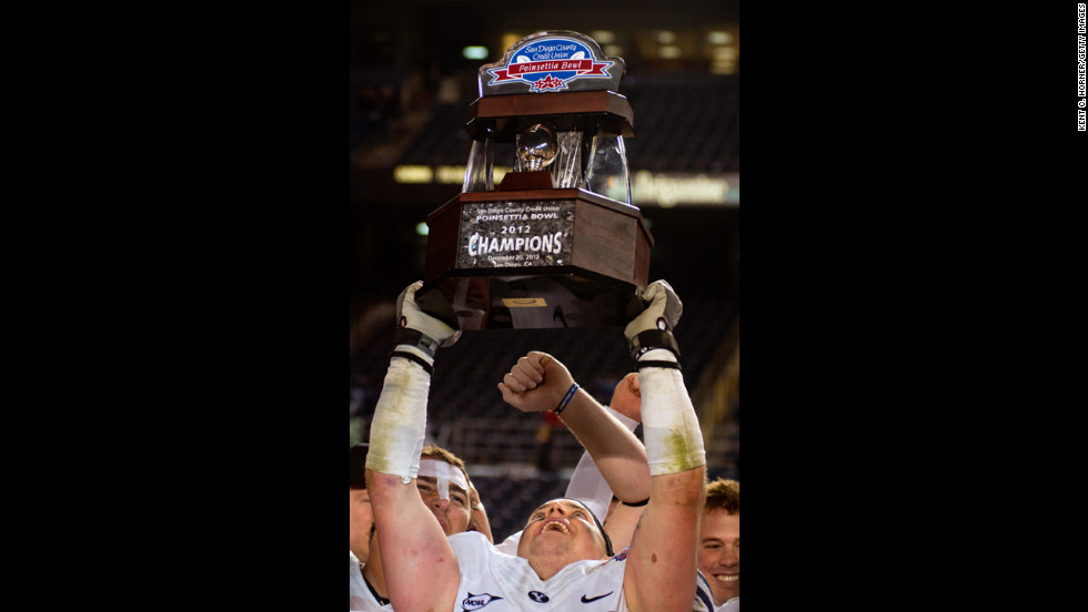 Brandon Ogletree of the BYU Cougars hoists the championship trophy after beating the San Diego State Aztecs 23-6 in the Poinsettia Bowl on December 20.