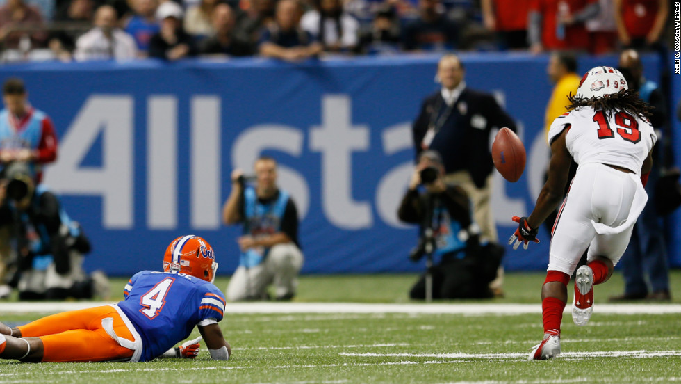 Terell Floyd of the Louisville Cardinals intercepts the ball and scores a touchdown as Andre Debose of the Florida Gators falls to the field after missing the catch in the first quarter on January 2.