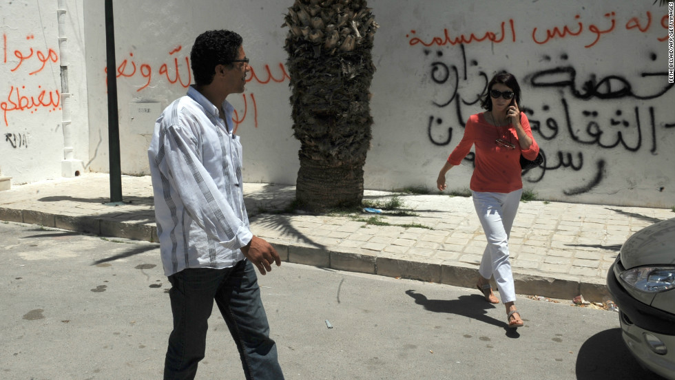 "Tunis residents walk past graffiti left by rioters on a building housing a controversial art exhibition in the Tunisian capital in June 2012. The graffiti  messages read: ""God is great,,"" ""Non-believers have no place in Tunisia"" and ""You are enemies of God."""