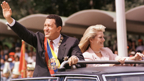 President Chavez greets supporters with his then-wife, Marisabel Rodriguez de Chavez, beside him as he arrives to preside over a parade in his honor on February 4, 1999, in Caracas. Chavez was sworn in as president on February 2.