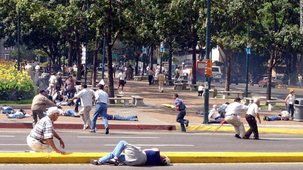 People try to take shelter from gunshots fired near Altamira Square in Caracas on August 16, 2004. At least three people were wounded by gunshots after Chavez supporters fired on opposition demonstrators, police said. A vote to recall Chavez as president failed on August 15.