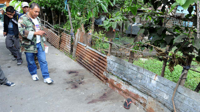 Police investigate the scene of a gun battle in Kawit, about 40 km south of Manila on January 4, 2013.