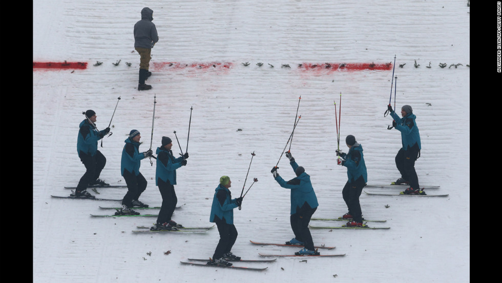 Maintenance crew members gesture as they prepare the landing zone with their skis on January 4.