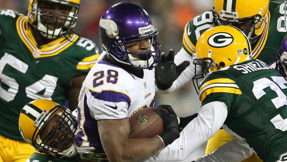 Running back Adrian Peterson of the Minnesota Vikings is tackled by several Green Bay Packers during an NFC Wild Card playoff game Saturday, January 5, in Green Bay, Wisconsin.