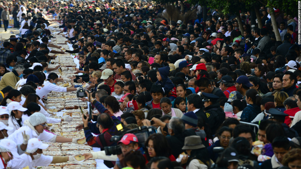 "People gather to get a piece of the traditional ""Rosca de Reyes,"" or Mexican epiphany bread, in Mexico City on Thursday, January 3, The world's biggest ""Rosca de Reyes,"" weighing 10 metric tons, was distributed among 200,000 people at Zocalo Square in the Mexican capital."