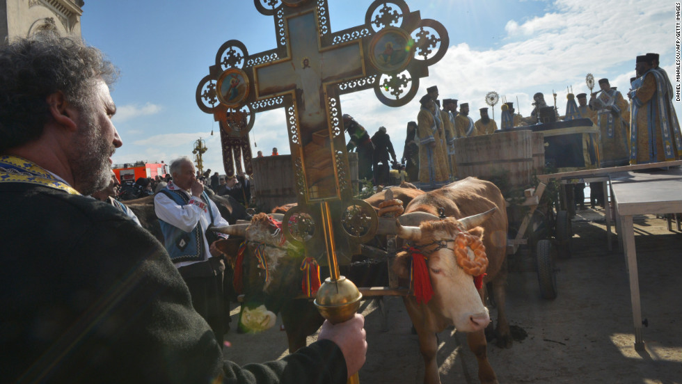 A priest holds a cross next to an ox-drawn cart transporting water to be consecrated during the Epiphany service in Constanta City on Sunday.