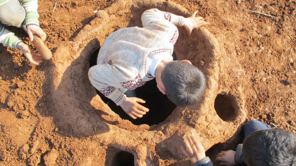 In the Bab al-Salam camp on the Syrian-Turkish border, Syrian refugees try to carry on their lives through the bitter winter. Muhammad Zafir, 13, steps inside the hole he dug with two of his friends: a bomb shelter they have made for children.