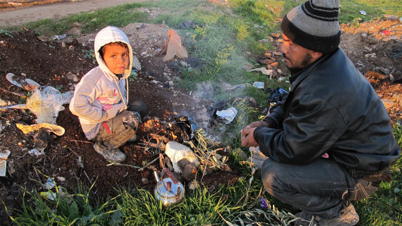 Abo Ahmad lit up plastics for warmth with his child.