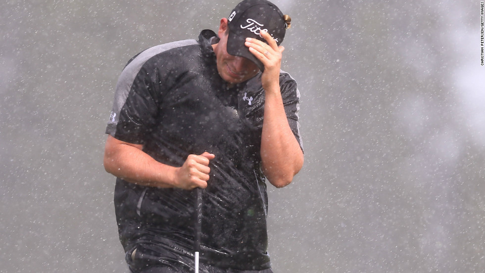 Scott Stallings shields himself from the wind and rain as he attempts to putt on the second hole green on Friday.