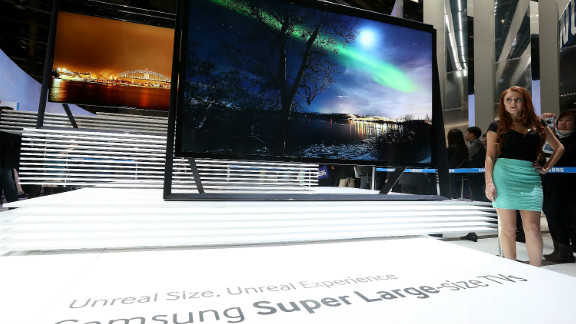 A model stands next to a display of new large-format Samsung televisions at Samsung