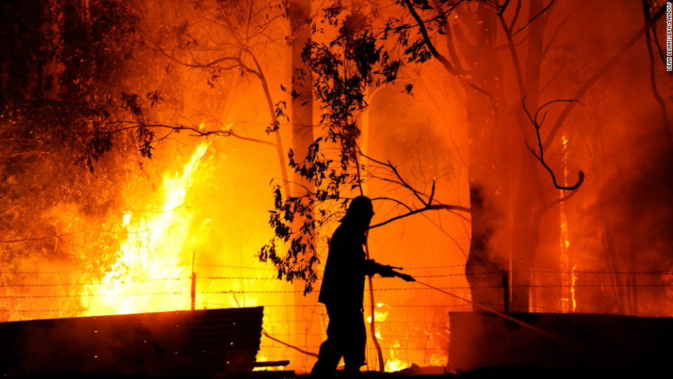 A firefighter battles the flames of the Dean's Gully fire at a property near the town of Wandandian in New South Wales, on January 8.