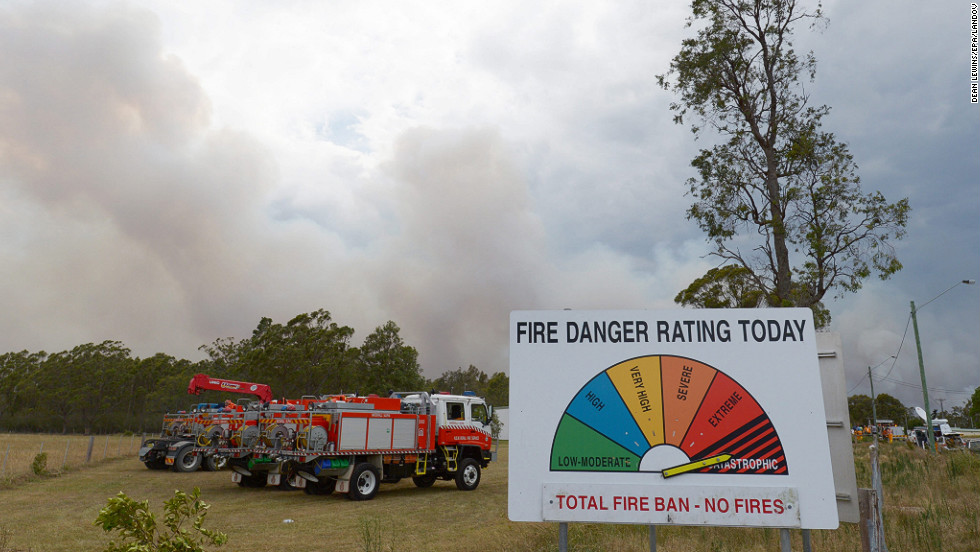 A fire danger rating sign set to catastrophic stands near fire trucks as smoke billows into the sky on the outskirts of Wandandian on January 8. On Tuesday afternoon, more than 130 fires were burning throughout NSW, according to the NSW Rural Fire Service.