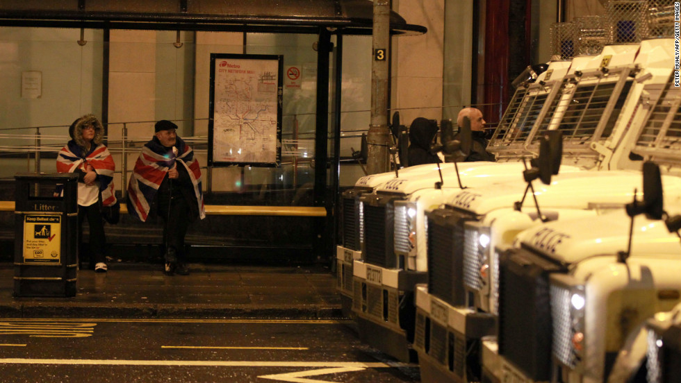 A couple sit at a bus stop wrapped in British union flags as police vehicles protect the back of the City Hall on Monday.