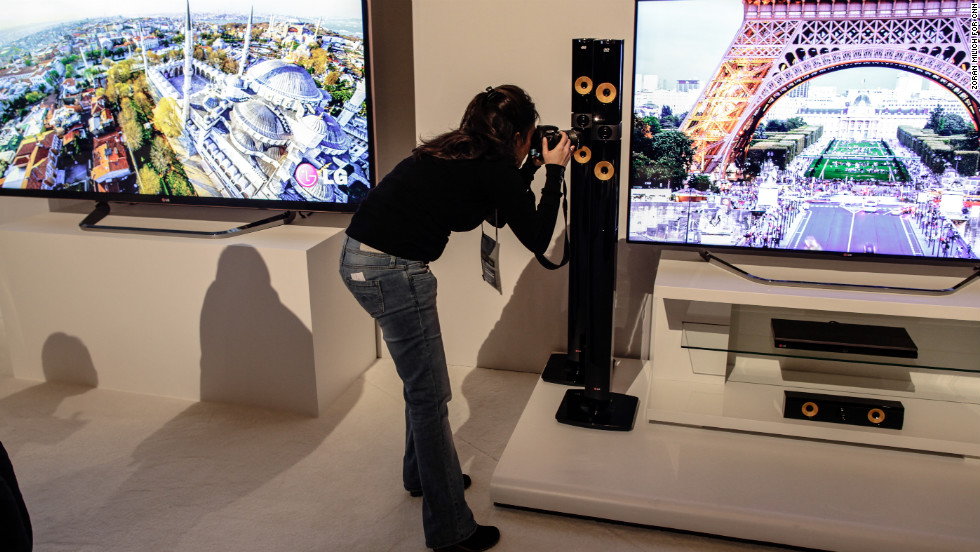 A journalist photographs new LG products at the first CES press conference Monday morning.