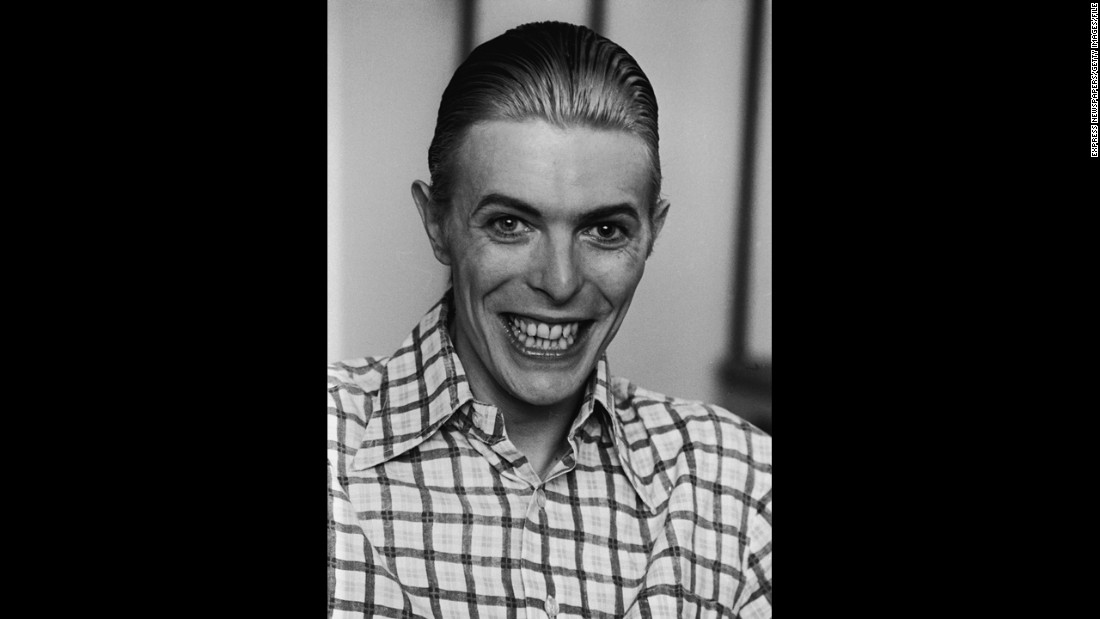 Bowie grins broadly, wearing a plaid shirt with his hair slicked back, circa 1980.